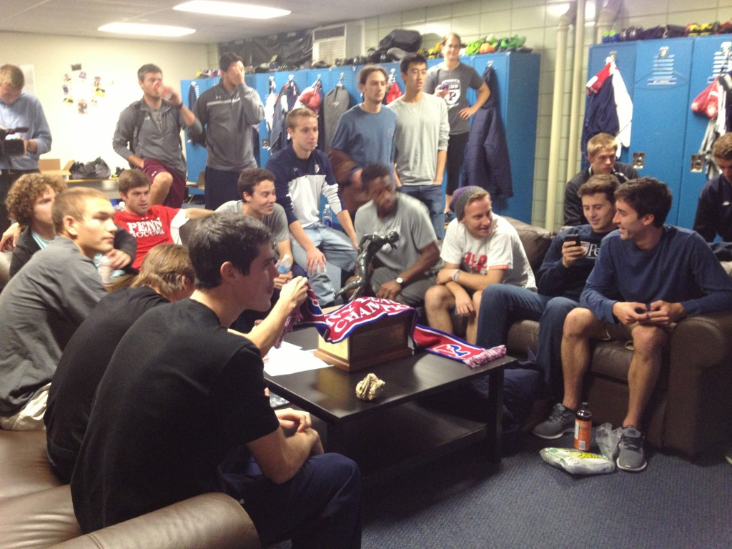 Penn soccer players and coaches watch the NCAA selection show, with their Ivy League championship trophy sitting on the table beside them.
