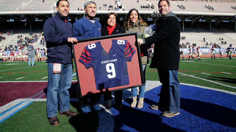 Bagnoli poses with his wife and three kids as he's presented with a framed jersey. The 9 is for the number of Ivy League championships he won at Penn.