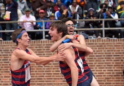Thomas Awad, holding the baton, celebrates with teammates right after crossing the finish line first.