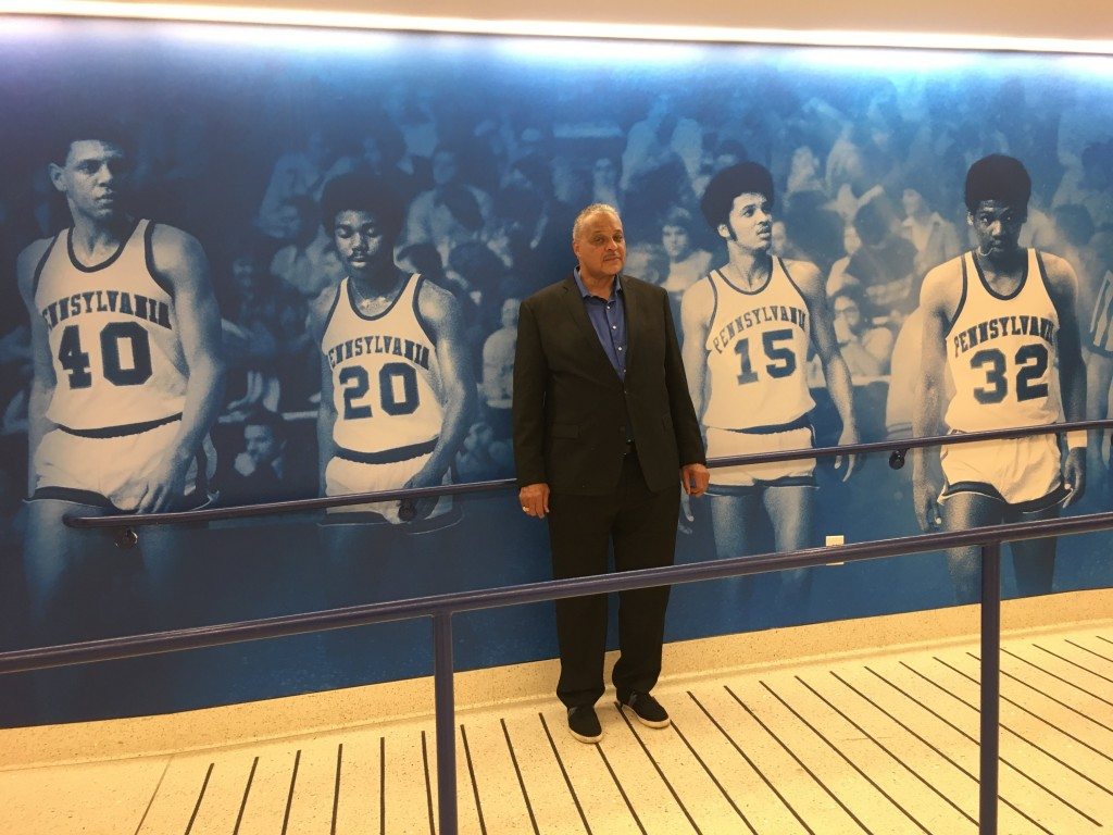 Tony Price, posing next to an old photo of himself, in the newly decorated Tse Center Atrium.