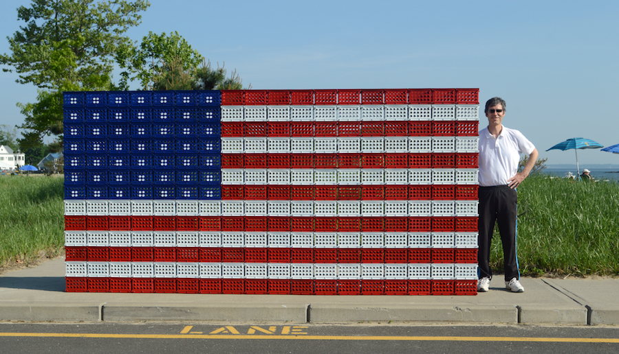 Robert Carley stands next to his creation: a giant flag made out of red, white, and blue plastic baskets