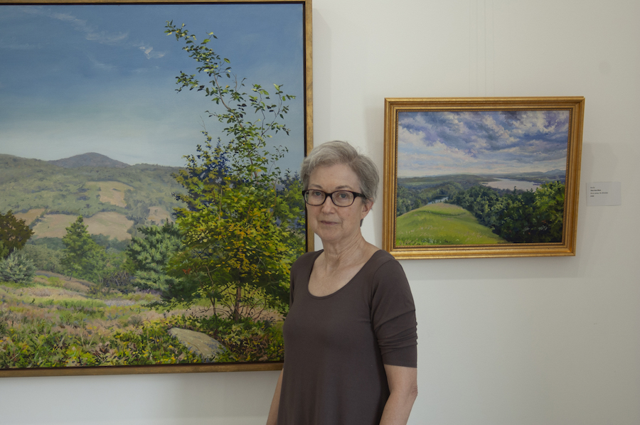 Bepe stands in front of two landscape paintings by Kim Do