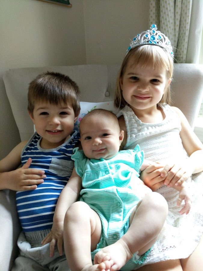 Samuel J. Fetchero W'03's children, Caleb, Eva, and Noelle, smile while seated on a couch.
