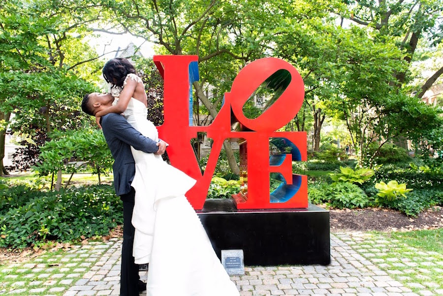 The groom, Kevin Osayi Osagie EE'10 EAS'10, lifts Sonie Kama Guseh C'10 in her wedding gown in front of the LOVE statue on campus.