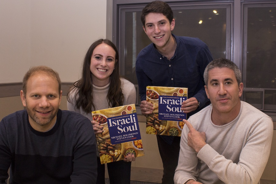 Steven Cook and Michael Solomonov sit while two students display their cookbook behind them.