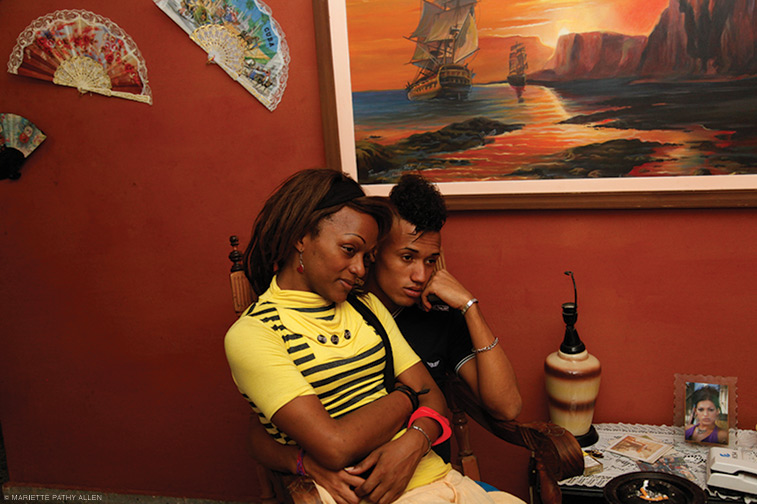 """""""Nomi and Miguel, partners, watching television at Malu's apartment, Havana, Cuba."""" 2013. From TransCuba (2014)."""