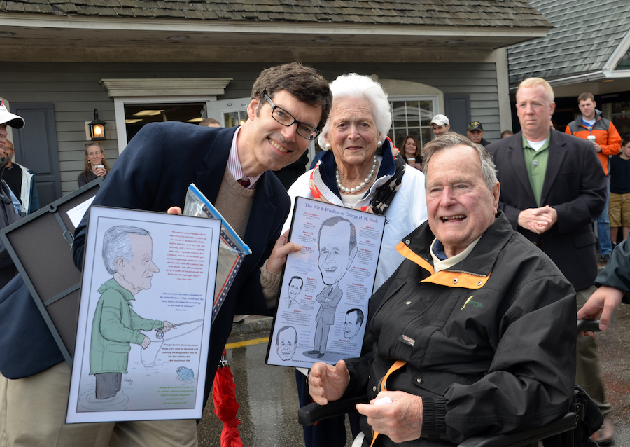 Robert Carley poses with George H. W. Bush and Barbara Bush, holding two illustrations