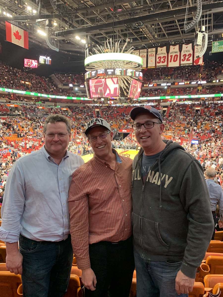 Roy, Keith, and Steven pose in the stands of the arena with the scoreboard above their heads.