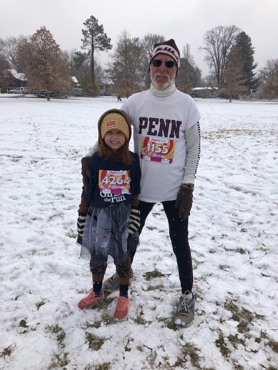 Steve and his granddaughter pause before the race, bundled up in winter clothes, with snow on the ground.