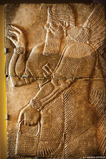 A limestone relief, 883-859 BCE, depicting a winged genie, that decorated a room in the palace of the Syrian ruler Ashurnasirpal II, both from Nimrud, Iraq.