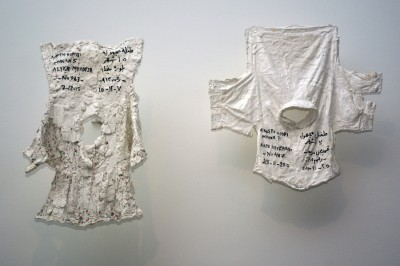 "In Issam Kourbaj's ""Lost,"" children's clothing acts as a gravestone for the child who didn't make it across the Aegean Sea. Descriptions and dates of death are written in both Arabic and Greek: ""Unknown girl, 15 months old, white blouse, No. 963, 7-12-2015"" and ""Unknown boy, 17 months old, checked shirt, No. 487, 25-11-2015."""