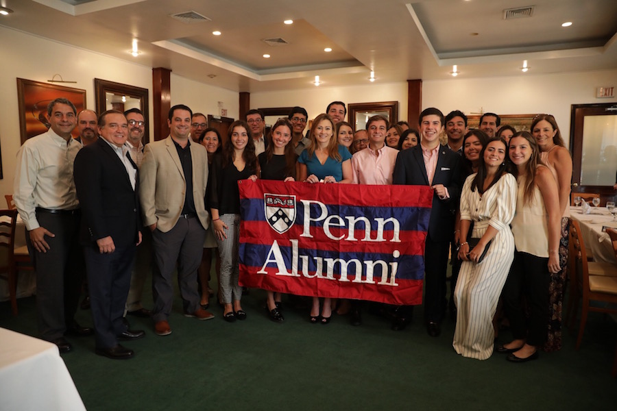 The Penn Alumni Club of Puerto Rico stands together holding a red and blue Penn Alumni flag