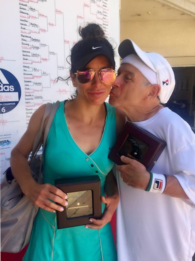 Dr. Richard Cohen C'69 plants a kiss on his his daughter Julia after the tennis match, while they hold their trophies.