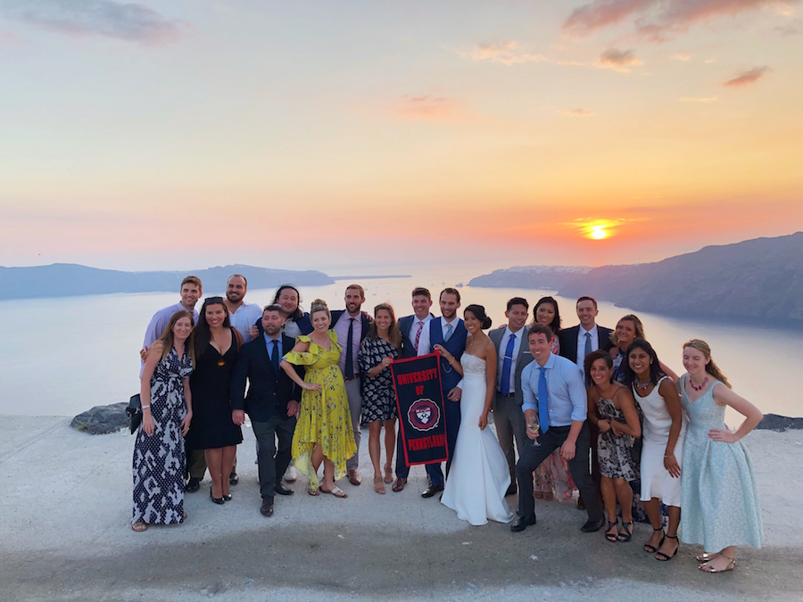 Jessica and Timothy stand with their wedding party on the beach during a sunset.