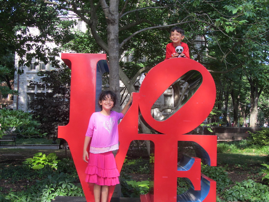Gamaliel Isaac's children play on the Love statue.