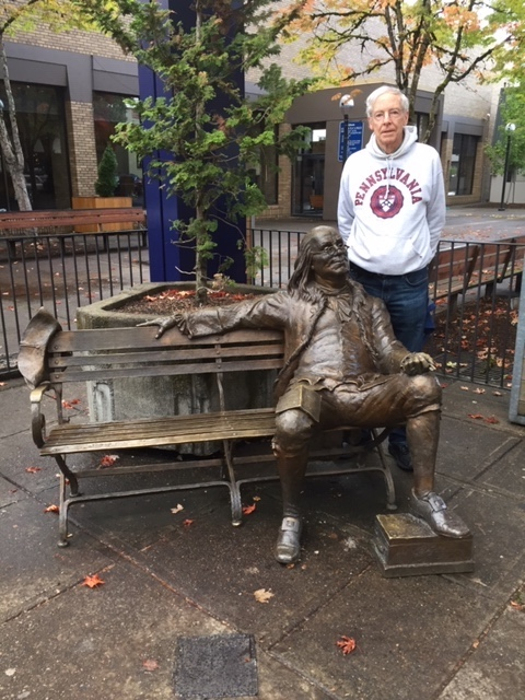 Warren Peterson stands next to a statue of Ben Franklin sitting on a bench.