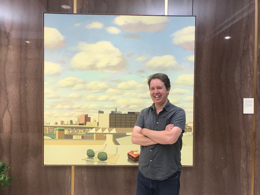William Hudders stands smiling in front of one of his paintings