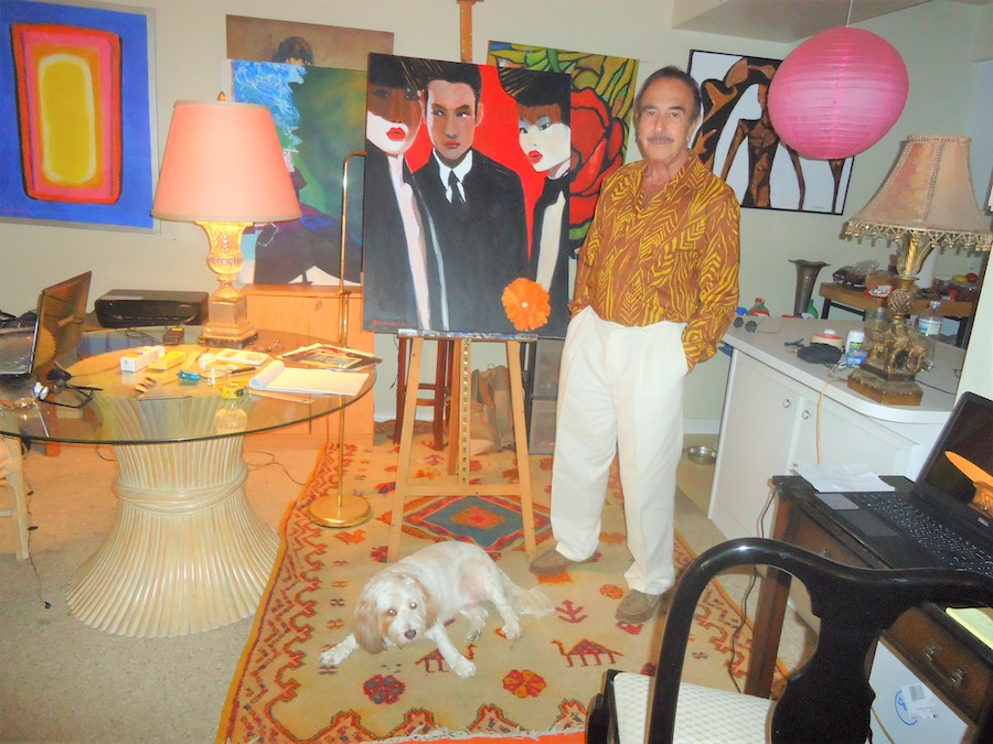 Ron stands in his art studio in front of a painting of two female figures with broad, black hats and a man in a suit. A small white dog is at Ron's feet.