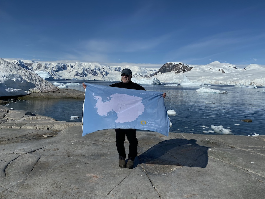 Art Gertel C'75 holds a flag in front of a lake in Antarctica.