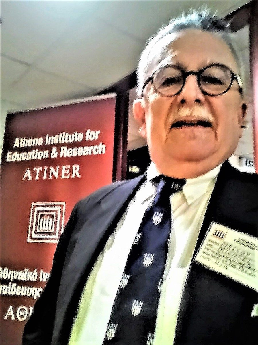 Michael P. Malloy L'76 takes a selfie in front of the conference sign.