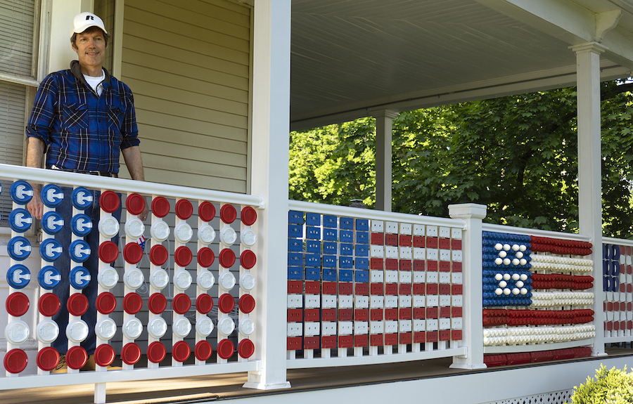 Robert Carley C'82 stands on a porch that contains his artwork: flags created along the porch banisters made of recycled coffee cups and lids.