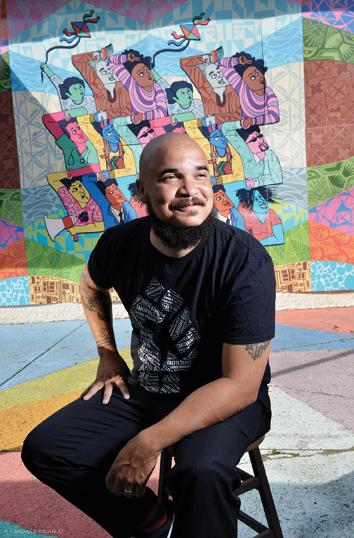Photo of Chaz Howard at 38th and Lancaster, in front of a mural.