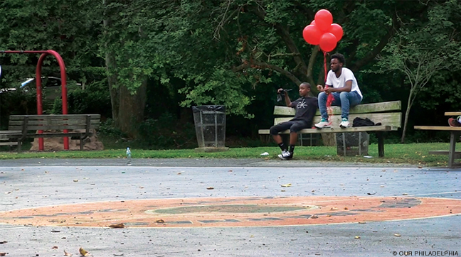Still from Our Philadelphia, two boys with red balloons sitting on a park bench.