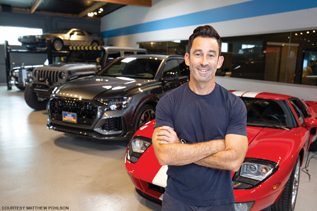 Photo of Matthew Pohlson standing in front of cars to be auctioned as fundraising prizes