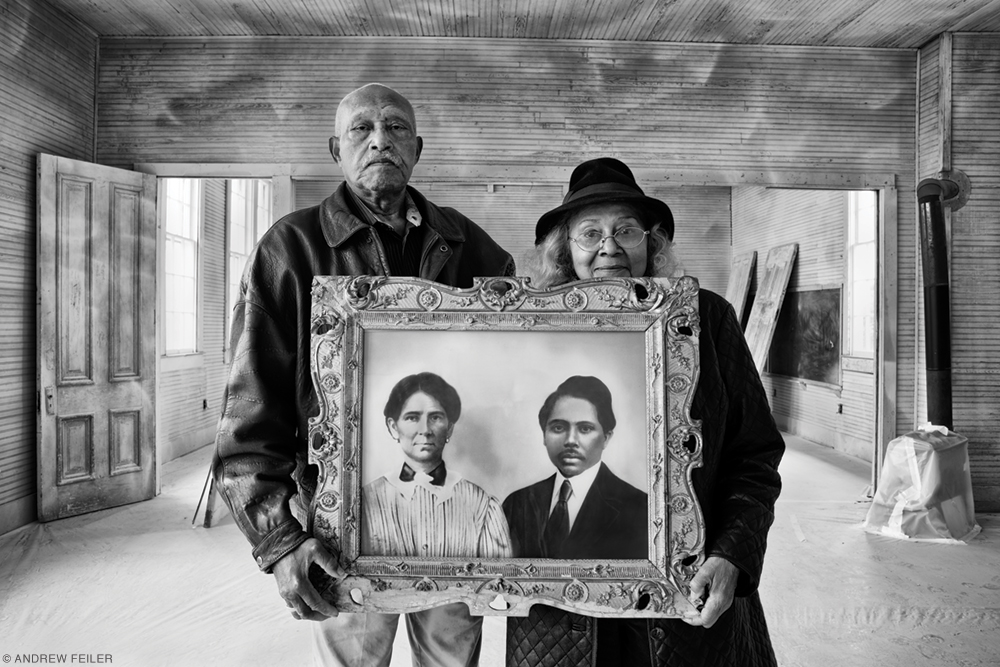 Photo of Elroy and Sophia Williams holding a portrait of Sophia's grandparents