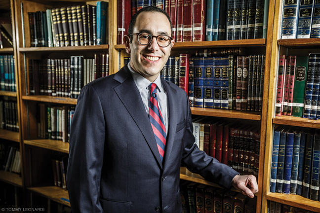 Photo of Rabbi Mike Uram in front of bookshelves at Penn Hillel