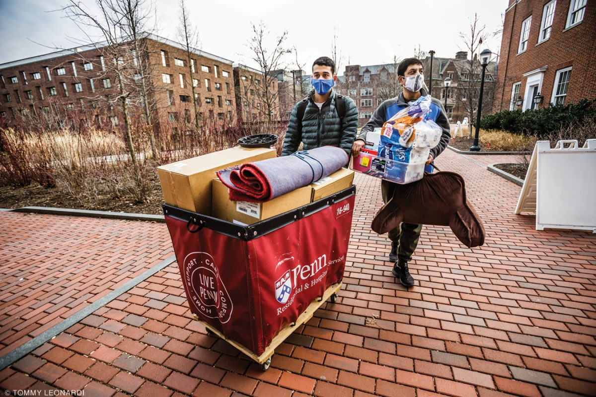 Photo of student and father moving belongings into dorm
