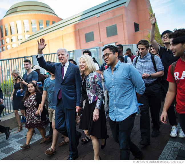 Photo of President Joe Biden with Amy Gutmann on a walk through campus in 2017 with students in tow.